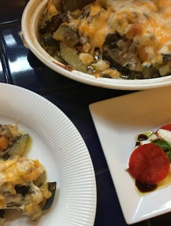 vegetable casserole next to a plate of caprese salad
