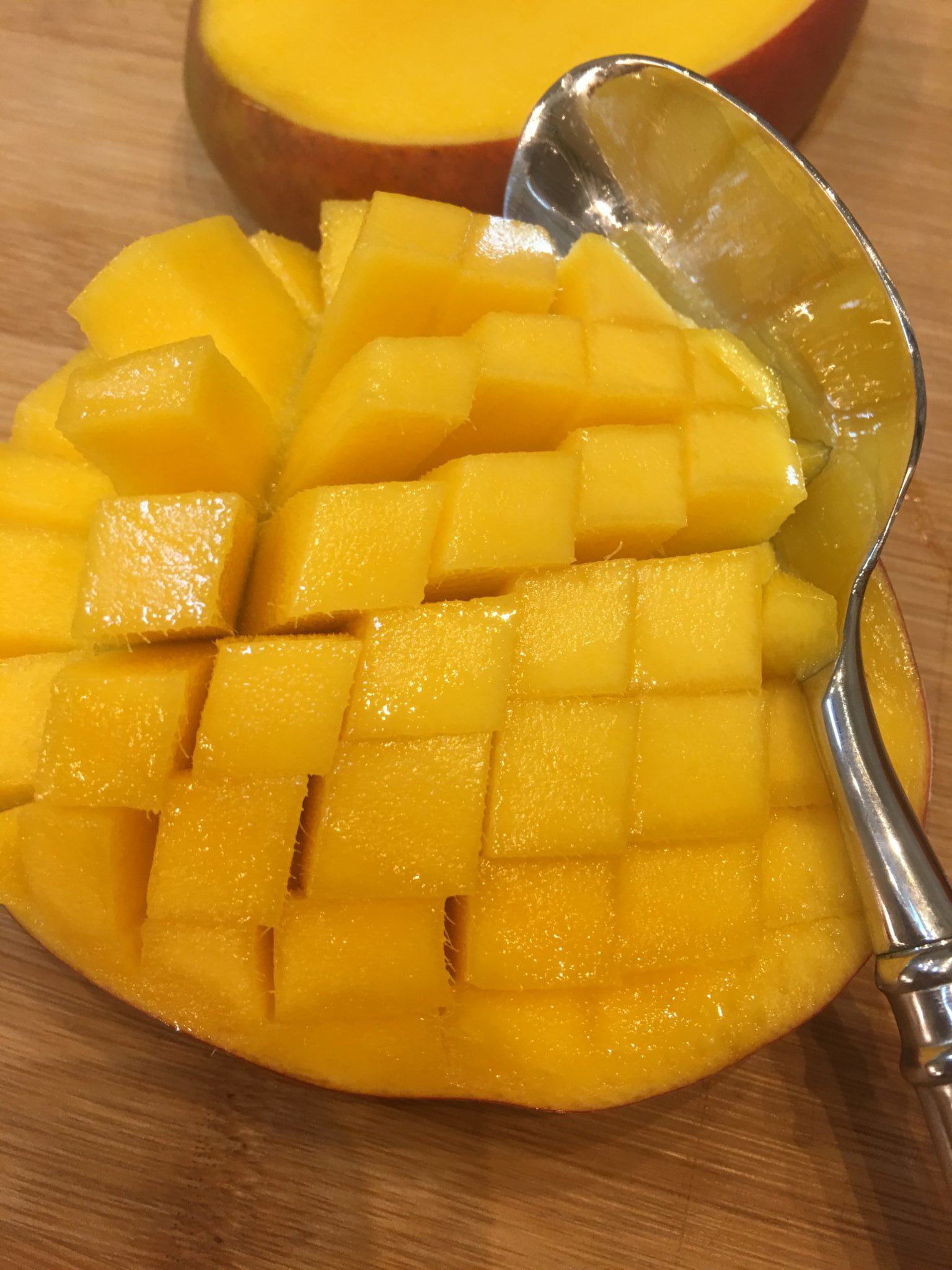 Use a spoon to get the meat from a mango