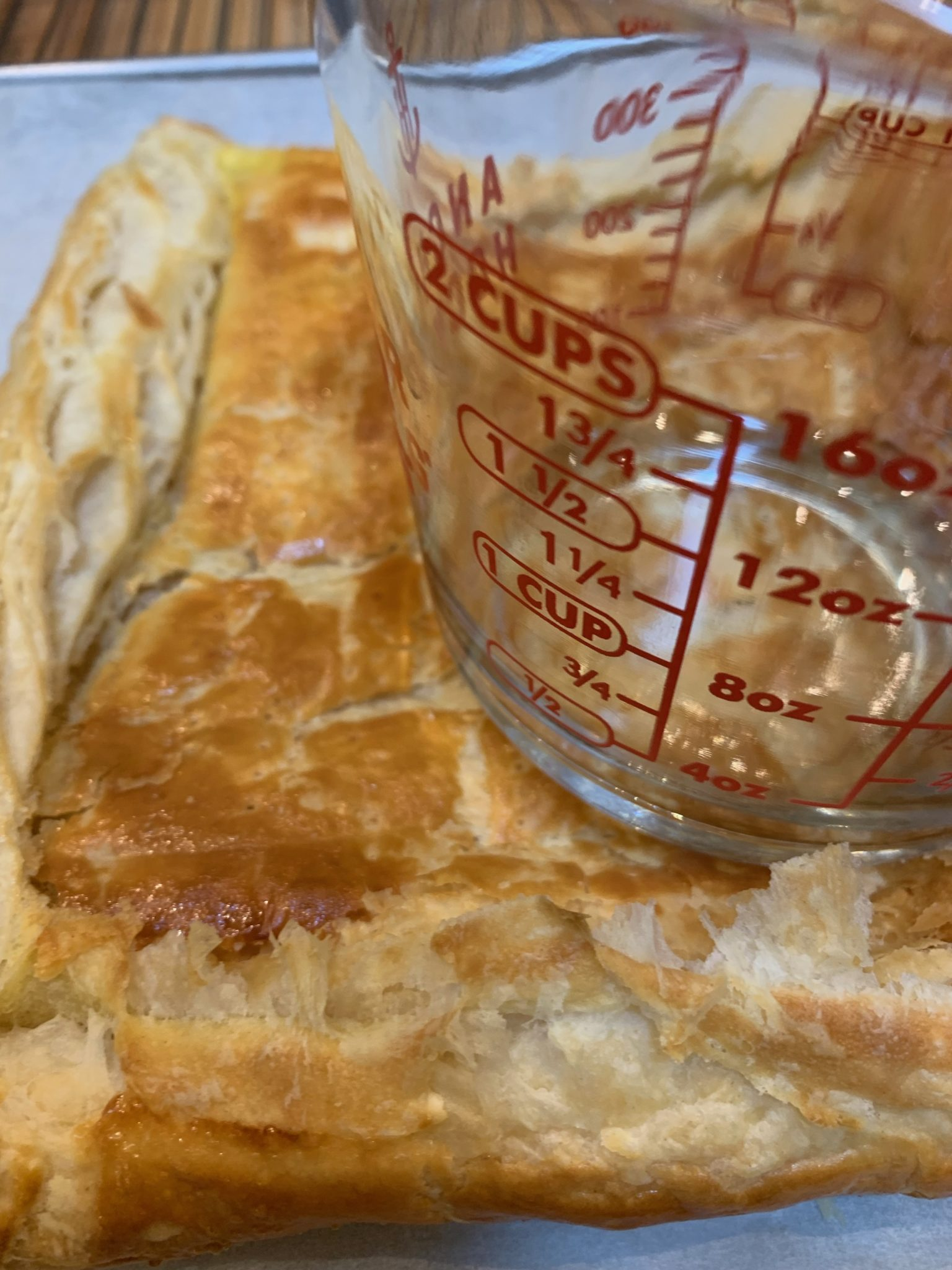 Falltening the center of the puff pastry tart with a measuring cup