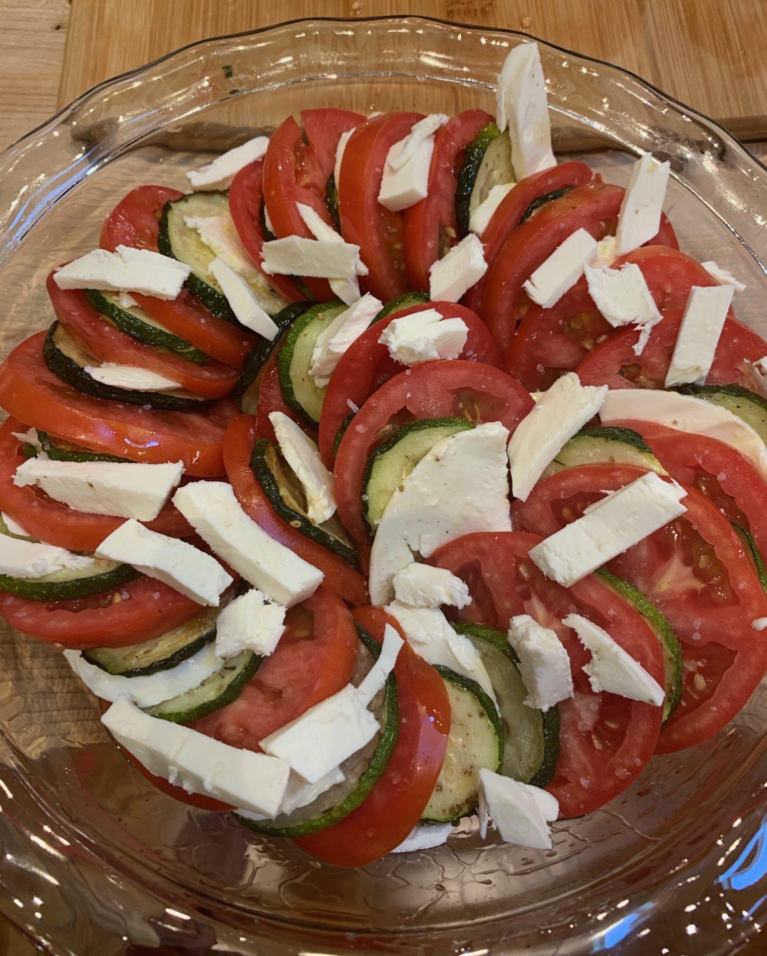 Slices of zucchini, tomato and mozzarella are layers in a glass pie plate before baking