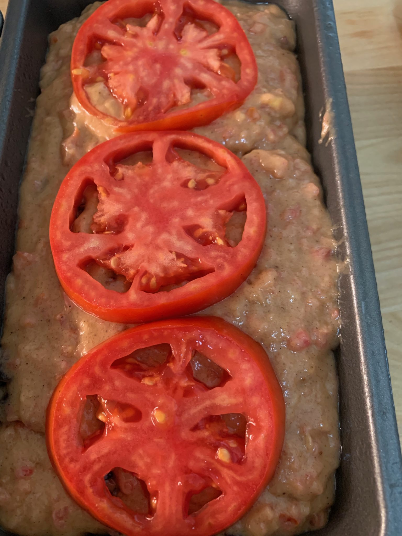 Tomato bread batter topped with sliced tomatoes