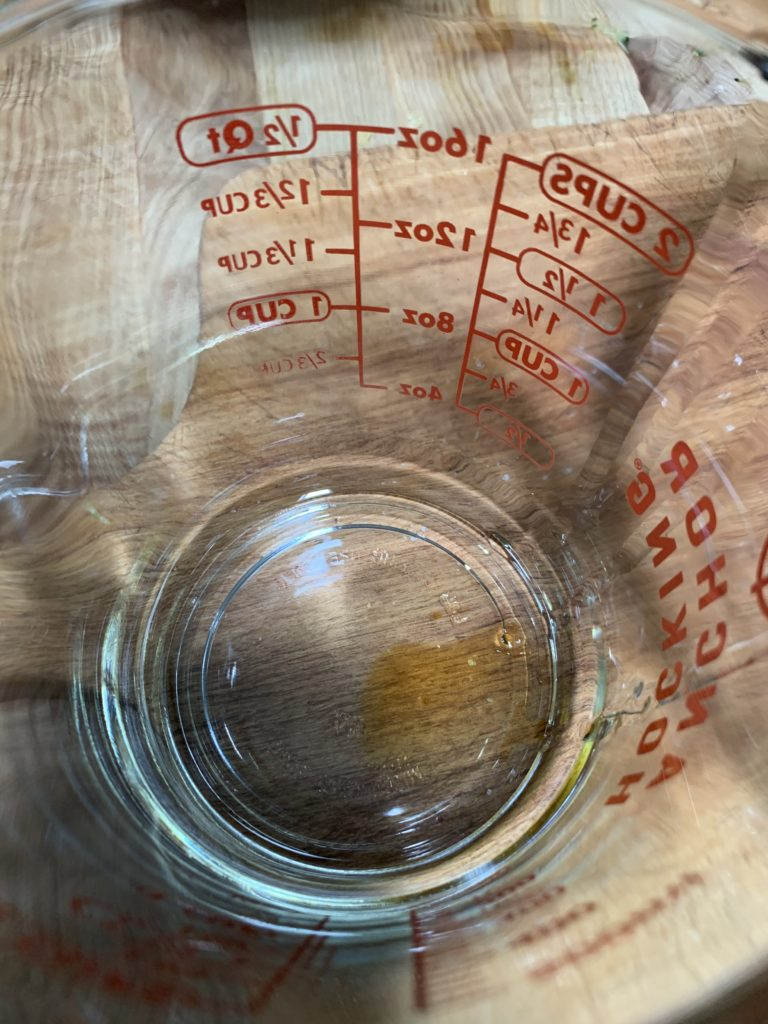 An empty measuring cup with just a tiny amount of residual maple syrup